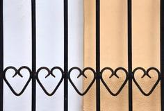 Κιγκλίδωμα επεξεργασμένος-σιδήρου με τις καρδιές μπροστά από έναν τοίχο στοκ φωτογραφία με δικαίωμα ελεύθερης χρήσης