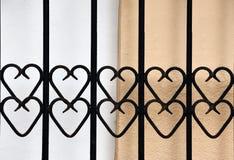 Κιγκλίδωμα επεξεργασμένος-σιδήρου με τις καρδιές μπροστά από έναν τοίχο στοκ φωτογραφίες
