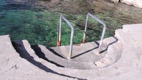 Κιγκλιδώματα για την κολύμβηση και σκαλοπάτια στην παραλία της θάλασσας Σκαλοπάτια με τα κιγκλιδώματα που οδηγούν στη θάλασσα Κύμ απόθεμα βίντεο