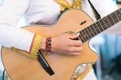 Κιθάρα και musician& x27 στενός επάνω χεριών του s Στοκ Εικόνα