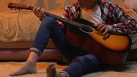 Κιθάρα παιχνιδιού άσκησης εφήβων στο σπίτι, που γράφει το τραγούδι για τη σχολική απόδοση απόθεμα βίντεο