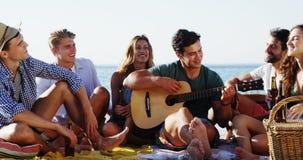Κιθάρα παιχνιδιού ατόμων για τους φίλους που κάθονται στην παραλία 4k φιλμ μικρού μήκους