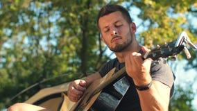 Κιθάρα παιχνιδιού ατόμων στο δάσος απόθεμα βίντεο