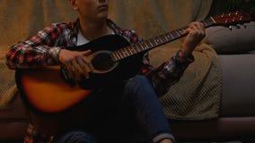 Κιθάρα παιχνιδιού εφήβων αριστεροχείρων και τραγούδι τραγουδιού στο σπίτι μόνο, μπαλάντα βράχου απόθεμα βίντεο
