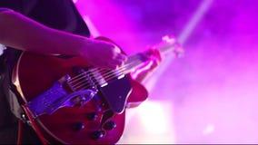 Κιθάρα παιχνιδιού κιθαριστών στη σκηνή φιλμ μικρού μήκους