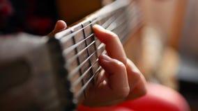Κιθάρα παιχνιδιού κοριτσιών εφήβων στο σπίτι Κλείστε επάνω του χαριτωμένου εφήβου στο εσωτερικό σε έναν hoody γρατζουνώντας μαλακ φιλμ μικρού μήκους