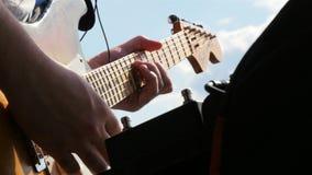 Κιθάρα παιχνιδιών μουσικών κινηματογραφήσεων σε πρώτο πλάνο στο κεντρικό τετράγωνο ψυχαγωγίας απόθεμα βίντεο