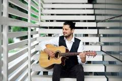 Κιθάρα παιχνιδιού ατόμων στα σκαλοπάτια Στοκ εικόνες με δικαίωμα ελεύθερης χρήσης