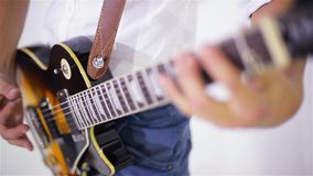 Κιθάρα παιχνιδιού ατόμων στο στούντιο σε ένα άσπρο υπόβαθρο, κινηματογράφηση σε πρώτο πλάνο φιλμ μικρού μήκους