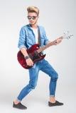 Κιθάρα παιχνιδιού καλλιτεχνών στο στούντιο θέτοντας να κοιτάξει μακριά Στοκ εικόνα με δικαίωμα ελεύθερης χρήσης
