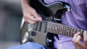 Κιθάρα παιχνιδιού κιθαριστών χεριών ατόμων υπαίθρια Κινηματογράφηση σε πρώτο πλάνο απόθεμα βίντεο