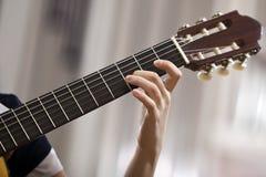 Κιθάρα παιχνιδιού κοριτσιών χεριών Στοκ Εικόνες