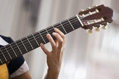 Κιθάρα παιχνιδιού κοριτσιών χεριών Στοκ Εικόνα
