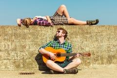 Κιθάρα παιχνιδιού νεαρών άνδρων στη φίλη του από την παραλία Στοκ Εικόνες