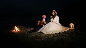 Κιθάρα παιχνιδιού νεόνυμφων στη νύχτα στην πυρά προσκόπων απόθεμα βίντεο