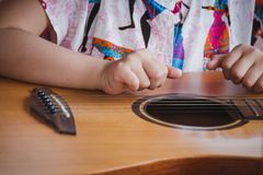 Κιθάρα παιχνιδιού παιδιών κινηματογραφήσεων σε πρώτο πλάνο Έννοια του liftstyle, της εκμάθησης, του χόμπι, του μουσικού, του ονεί στοκ εικόνες