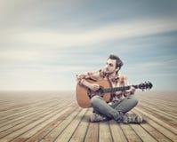 Κιθάρα παιχνιδιού στην ξύλινη γέφυρα στοκ φωτογραφία με δικαίωμα ελεύθερης χρήσης