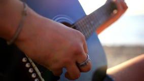 Κιθάρα παιχνιδιού χεριών μουσικών στην παραλία κατά τη διάρκεια απόθεμα βίντεο
