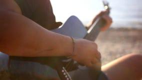 Κιθάρα παιχνιδιού χεριών μουσικών στην παραλία κατά τη διάρκεια φιλμ μικρού μήκους