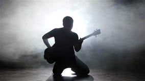 Κιθάρα παιχνιδιού bassist νεαρών άνδρων στα γόνατά του κίνηση αργή φιλμ μικρού μήκους