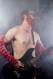 Κιθαρίστας με την ηλεκτρική κιθάρα μαύρη, φορώντας το χρώμα προσώπου και το κόκκινο Στοκ εικόνα με δικαίωμα ελεύθερης χρήσης