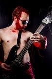 Κιθαρίστας με την ηλεκτρική κιθάρα μαύρη, φορώντας το χρώμα προσώπου και το κόκκινο Στοκ Εικόνες