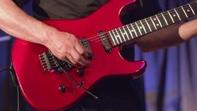 Κιθαρίστας μολύβδου ατόμων που παίζει την ηλεκτρική κιθάρα στη σκηνή συναυλίας απόθεμα βίντεο