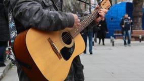 Κιθαρίστας που παίζει την ακουστική κιθάρα στην οδό φιλμ μικρού μήκους