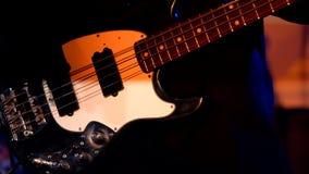 Κιθαρίστας που παίζει τη βαθιά κιθάρα στη ζωντανή συναυλία απόθεμα βίντεο
