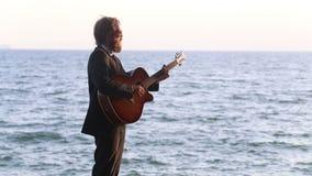 κιθαρίστας στα μαύρα παιχνίδια κοστουμιών ενάντια στη θάλασσα απόθεμα βίντεο