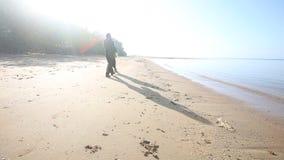 κιθαρίστας στους μαύρους περιπάτους κατά μήκος της παραλίας και τα παιχνίδια για το ξανθό κορίτσι απόθεμα βίντεο