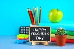 Κιμωλία κειμένων σε έναν πίνακα κιμωλίας: Ημέρα του ευτυχούς δασκάλου Σχολικές προμήθειες, γραφείο, βιβλία, μήλο στοκ φωτογραφία με δικαίωμα ελεύθερης χρήσης