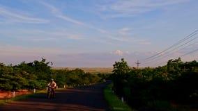 Κινήσεις καμερών κατά μήκος του σκιερού δρόμου μεταξύ του πράσινου countryscape φιλμ μικρού μήκους