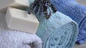 Κινήσεις καμερών κατά μήκος των καθαρών και φρέσκων πετσετών, lavand και των σαπουνιών στο ξύλινο υπόβαθρο