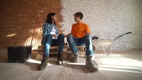Κινήσεις νέες ζευγών σε ένα νέο σπίτι Η σύζυγος και ο σύζυγος κάθονται στις αναπνευστικές συσκευές Κουρασμένος μετά από την εργάσ φιλμ μικρού μήκους