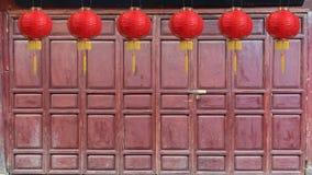 Κινεζικά νέα φανάρια έτους στην ξύλινη διπλώνοντας πόρτα φιλμ μικρού μήκους