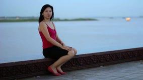 κινεζικά σταλμένα μουσική φιλιά ακούσματος επιχειρησιακών γυναικών στην όχθη ποταμού απόθεμα βίντεο