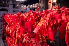 Κινεζικές κόκκινες κορδέλλες σε έναν φράκτη στο βουδιστικό ναό Στοκ φωτογραφία με δικαίωμα ελεύθερης χρήσης