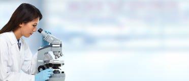 Κινεζική γυναίκα γιατρών με το μικροσκόπιο Στοκ Εικόνες