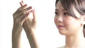 Κινεζική γυναίκα που εφαρμόζει την κρέμα στα χέρια απόθεμα βίντεο