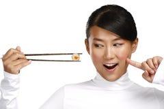 Κινεζική γυναίκα που παρουσιάζει ασιατικά τρόφιμα που χρησιμοποιούν chopstick Στοκ Φωτογραφία