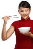 Κινεζική γυναίκα που παρουσιάζει ασιατικά τρόφιμα που χρησιμοποιούν chopstick Στοκ φωτογραφίες με δικαίωμα ελεύθερης χρήσης