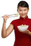Κινεζική γυναίκα που παρουσιάζει ασιατικά τρόφιμα που χρησιμοποιούν chopstick Στοκ Εικόνα