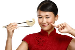 Κινεζική γυναίκα που παρουσιάζει ασιατικά τρόφιμα που χρησιμοποιούν chopstick Στοκ εικόνα με δικαίωμα ελεύθερης χρήσης