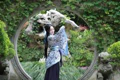 Κινεζική γυναίκα στο παραδοσιακό μπλε και άσπρο φόρεμα Hanfu που στέκεται στη μέση της όμορφης πύλης στοκ εικόνες