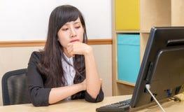 Κινεζική επιχειρηματίας στο γραφείο που εξετάζει το όργανο ελέγχου Στοκ Φωτογραφίες