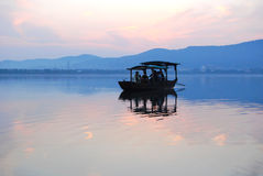 Κινεζική ξύλινη βάρκα που παρασύρει σε μια λίμνη στο ηλιοβασίλεμα Στοκ Εικόνες