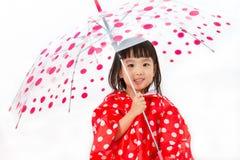 Κινεζική ομπρέλα εκμετάλλευσης μικρών κοριτσιών με το αδιάβροχο Στοκ εικόνα με δικαίωμα ελεύθερης χρήσης