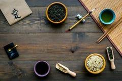 Κινεζική παραδοσιακή έννοια συμβόλων Τσάι, ρύζι, hieroglyph αγάπη, επιτραπέζιο χαλί μπαμπού, chopsticks, σόγια sause σκοτεινό σε  στοκ φωτογραφίες