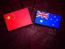 Κινεζική σημαία με την αυστραλιανή σημαία σε ένα κολόβωμα δέντρων που απομονώνεται Στοκ Φωτογραφία